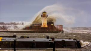 Waves crash over Ardrossan Harbour. Photo: William McKnight