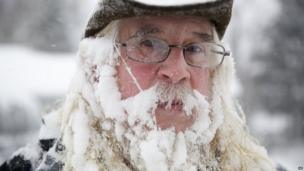 A man takes a break from blowing snow off of his driveway at his home in the US state of Michigan