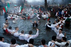 Bulgarian men dance in the icy waters of the Tundzha river during a celebration for Epiphany Day in the town of Kalofer