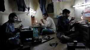 Goldsmiths work on gold ornaments at a workshop in Calcutta