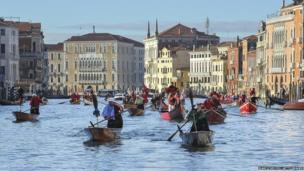 Rowers dressed in costume race along the Grand Canal for the Befana Regatta in Venice, Italy