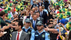 Security officers escort Australian Prime Minister Tony Abbott through cricket fans that have gathered to celebrate Australia's victory over England in the Ashes Test series at the Sydney Opera House during a ceremony on 7 January 2014