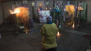 Woman praying at a makeshift chapel