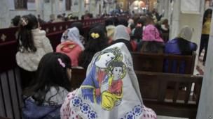 worshippers in church with woman wearing headscarf portraying Mary and Jesus