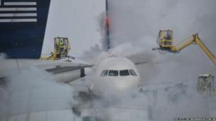 A passenger jet gets de-iced outside the terminal at Indianapolis International Airport