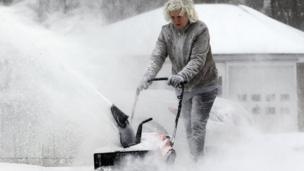Woman blowing snow away from driveway