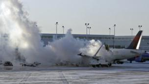 Plane is de-iced at Chicago airport.
