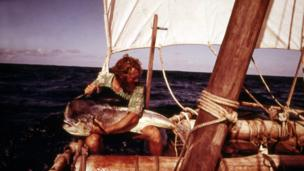 Mike Fitzgibbons holding a large fish, on the raft at sea
