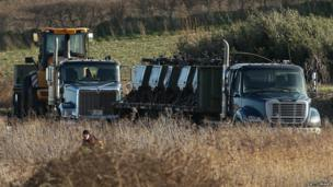 Equipment arrives on transport as military personnel and emergency services attend the scene at Cley next the Sea of USAF helicopter crash