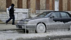 A man walks past a car partially covered in ice in Baltimore