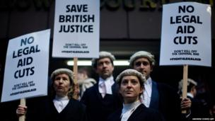 British legal professionals hold placards during a protest against cuts
