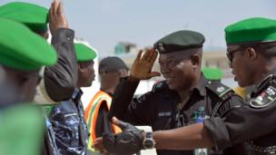 A Nigerian police commander saluting colleagues from the African Union police force on his arrival at the airport in Mogadishu, Somalia - Monday 6 January 2014