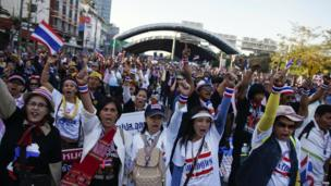 Anti-government protesters block the road at a major intersections in Bangkok on 13 January 2014
