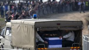 Israelis line the route as a military vehicle carries the coffin of former Israeli Prime Minister Ariel Sharon during his funeral at his family farm, 13 Jan
