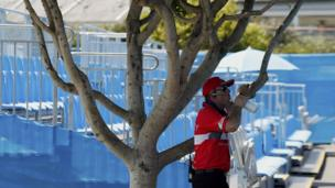 A security guard has a drink in the shade next to an empty stand after play was suspended at the Australian Open 2014 tennis tournament