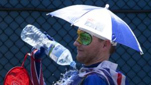 A spectators pours water over himself to cool down