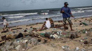 A man cleans up piles of the rubbish wash ashore on Kuta Beach in Indonesia