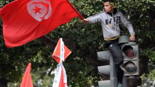 A man waving Tunisia's flag from the top of traffic lights during a rally in Tunis, Tunisia - Tuesday 14 January 2014