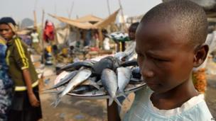 A boy selling fish in a displacement camp, Bangui airport, CAR - Wednesday 15 January 2014