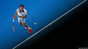 Roger Federer of Switzerland serves to Blaz Kavcic of Slovenia