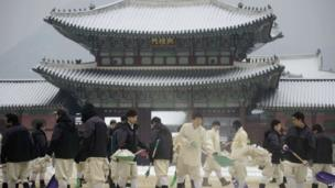 Workers clear snow inside the Gyeongbokgung Palace following overnight snowfall in Seoul on January 20, 2014. January is the coldest month in Seoul, with average temperatures falling some four degrees below freezing.