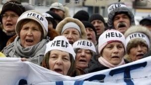 "Protesters wearing headbands reading ""Help"" shout slogans during an action entitled ""Impose sanctions - stop the violence"" in front of the European Union delegation in Ukraine in Kiev of January 20, 2014."