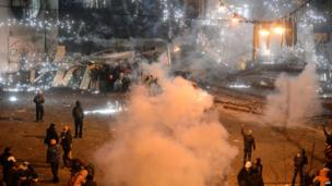 A smoke grenade explodes during clashes between police and protesters in central Kiev on 20 January 2014