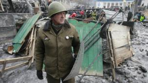 A demonstrator stands near a barricade during a rally held by pro-European integration protesters in Kiev, 21 January 2014.