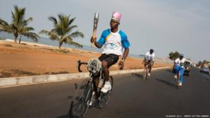 A cyclist takes the baton through the streets of Freetown, Sierra Leone