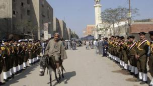 On Thursday, an Egyptian man on a donkey rides past a guard of honour (23 January 2014)