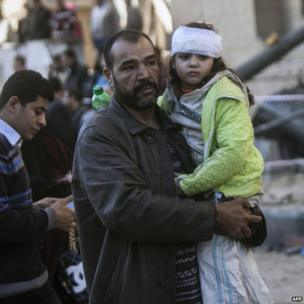 An Egyptian man carries an injured girl at the site of a car bomb explosion outside the Cairo police headquarters on 24 January 2014