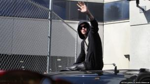 Singer Justin Bieber waves from atop an SUV as he leaves the Turner Guilford Knight Correctional Center