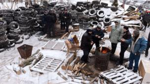 Protesters warm themselves at a brazier near a barricade, Lviv (25 Jan)