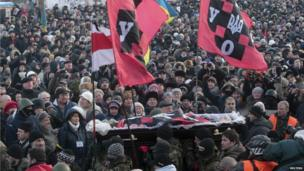 Supporters carry the coffin of Mikhail Zhiznevsky, an anti-government protester killed during recent rallies, during his funeral in Kiev on Sunday