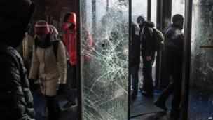 People walk past broken glass doors at Ukrainian House, which was taken over by anti-government protesters in Kiev in the early hours of Sunday morning