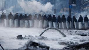 Riot police stand behind their shields at the site of clashes with anti-government protesters in Kiev