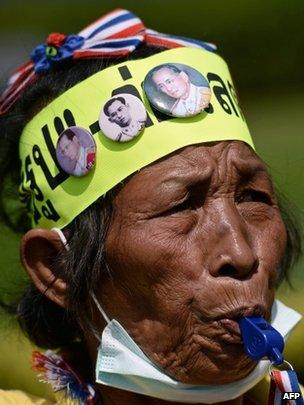 An elderly anti-government protester blows a whistle outside the army complex in Bangkok on 28 January