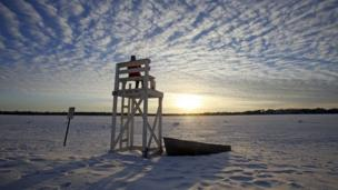 Lifeguard stand is surrounded by snow at a beach in Lake Calhoun, Minneapolis.