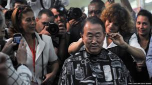 UN Secretary General Ban Ki-moon having his hair cut, surrounded by photographers in Cuba on 27 January