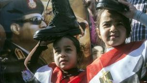 Two young Egyptian girls hold military boots on their heads in front of a photo of army chief Field Marshal Abdul Fattah al-Sisi. (27 Jan 2014)