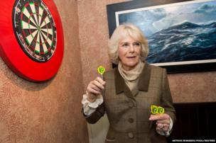 The Duchess of Cornwall holding darts