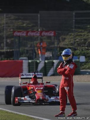 Fernando Alonso of Spain and Ferrari stands next to his car