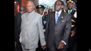 Zambian President Michael Sata (L) and Zimbabwe's President Robert Mugabe, hand-in-hand, at the African Union headquarters in Addis Ababa, Ethiopia - Thursday 30 January 2014