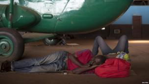 Men lying down beneath a helicopter in a hanger at Bangui airport, CAR - Thursday 30 January 2014