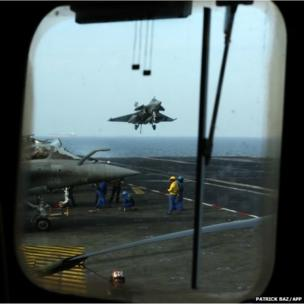 A French Navy Rafale jet fighter lands on the deck of the Charles de Gaulle aircraft carrier