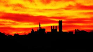 Glasgow University tower silhouetted against a fiery looking sky