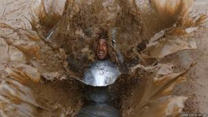 A competitor falls into muddy water during a Tough Guy event