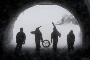 Volunteers walk through a tunnel from the gondola to the chairlift as preparations for the Sochi Winter Olympic