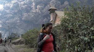 A woman flees as Mount Sinabung erupts near Bekerah village, in Karo district, North Sumatra, on February 1