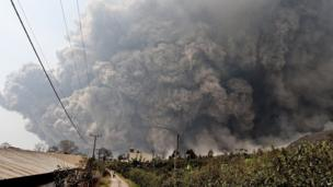 Mount Sinabung releases pyroclastic flows during an eruption as seen from Namantaran, North Sumatra, Indonesia, Saturday, Feb. 1,